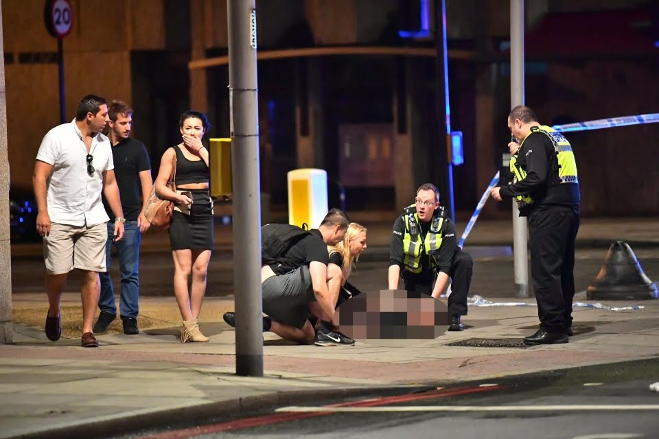 Officers are pictured treating a wounded victim after the attack in London Bridge